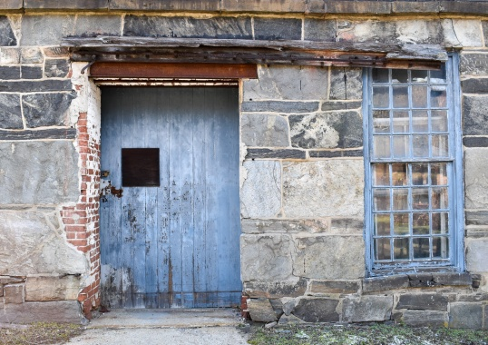Well-worn blue door. What's up with that square cut out in the door?